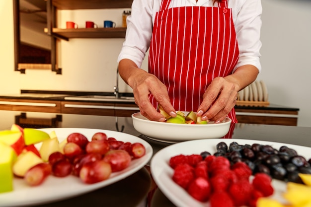Close-up shot van de hand van de chef-kok die stukjes fruit in smakelijke lekkere heerlijke zoete gemengde fruitsalade in witte kom op keukentafel zet. biologisch en natuurlijk gezondheidsvoedselconcept.