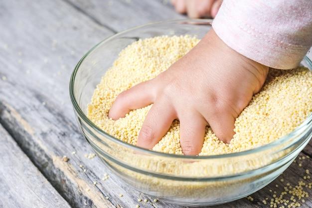 Close-up shot van de hand van een baby in een kom van verse hele amarath graan