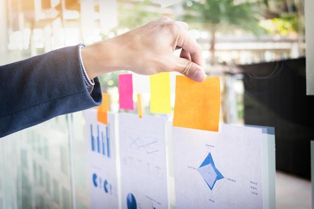 Close-up shot van de handen van de zakenman plakken lijm notities op de glazen muur in kantoor.