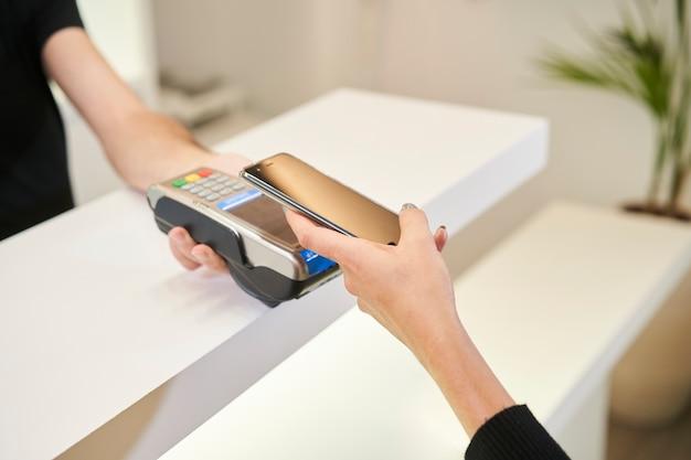 Close-up shot van de handen van een klant betalen met een smartphone