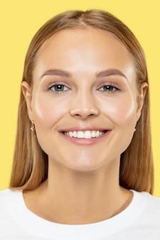 Close-up shot van de kaukasische jonge vrouw op gele studio