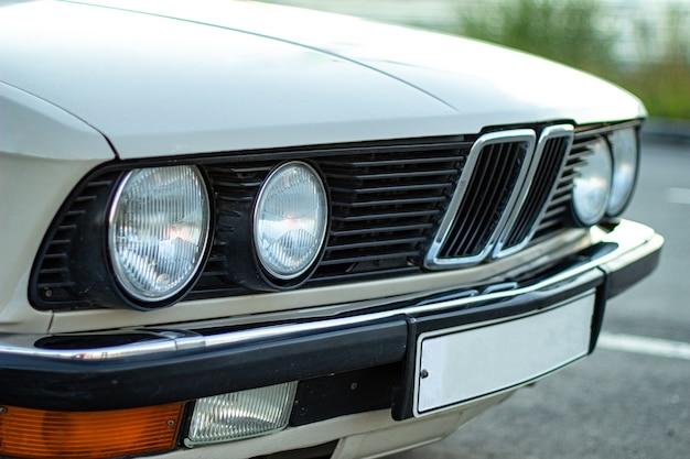 Close-up shot van de ronde koplampen van een witte vintage klassieke auto
