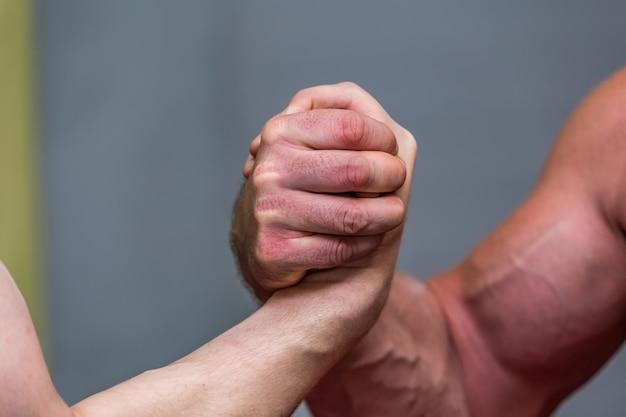 Close-up shot van de spieren van sterke mannen tijdens een armworstelgevecht