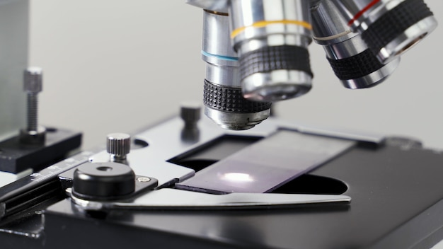 Close-up shot van de wetenschapper studies onderzoek van testmonster onder de microscoop in laboratorium.
