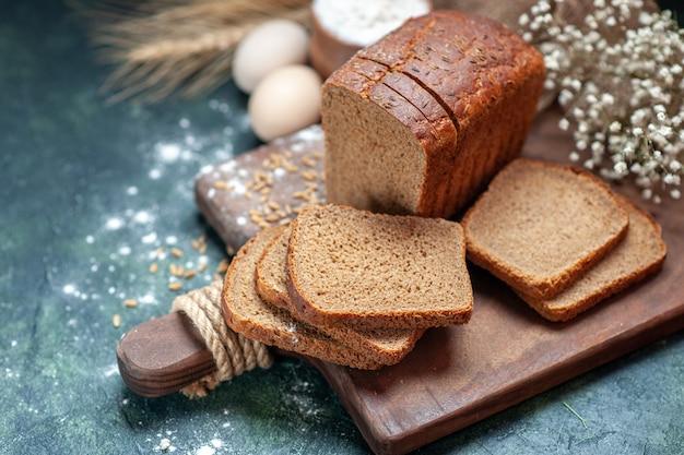 Close-up shot van dieet zwart brood tarwe op houten snijplank spikes bloem eieren meel in kom op blauwe achtergrond