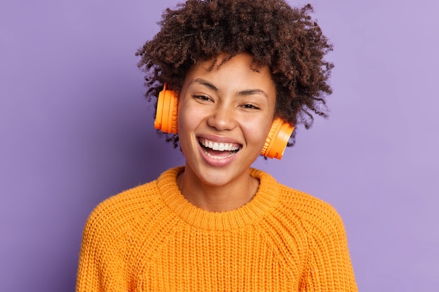 Close-up shot van dolblij afro-amerikaanse vrouw glimlacht in grote lijnen heeft krullend haar draagt stereo draadloze koptelefoon gekleed in gebreide oranje trui