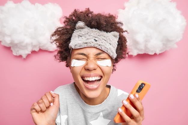 Close-up shot van dolblij etnische vrouw met krullend afro haar glimlach in het algemeen hand verhoogt voelt erg blij draagt pyjama maakt gebruik van mobiele telefoon voor surfen op sociale netwerken vormt binnen na het ontwaken