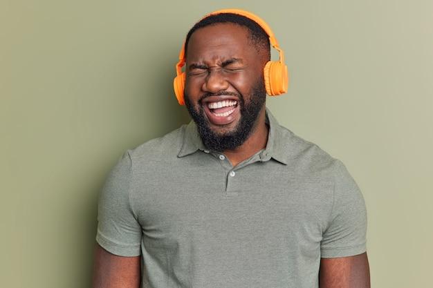 Close-up shot van dolblij man met witte tanden luistert radio via stereo koptelefoon hoort iets grappigs kan niet stoppen met lachen gekleed in casual t-shirt geïsoleerd over kaki muur