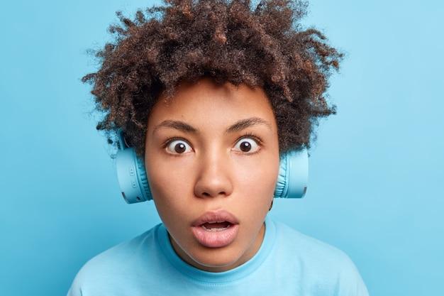 Close-up shot van donker gevild meisje met afro-haar staart afgeluisterde ogen heeft een geschrokken uitdrukking die geschokt is door iets dat muziek luistert via draadloze hoofdtelefoons geïsoleerd over blauwe muur. omg concept