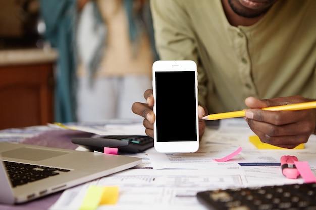 Close-up shot van donkere man handen met mobiele telefoon en potlood wijzend op het lege scherm