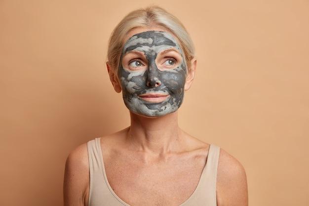 Close-up shot van doordachte europese vrouw past gezichtskleimasker toe en kijkt weg geeft om teint poses met blote schouders geïsoleerd op bruine muur