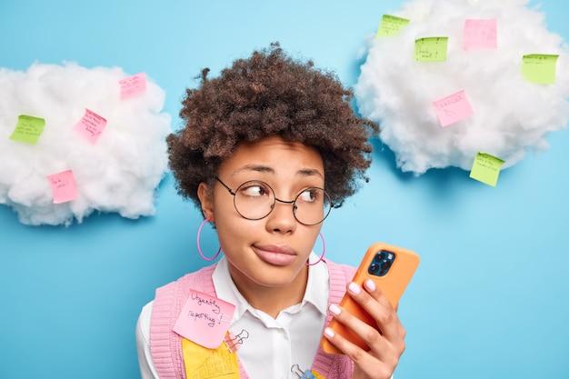 Close-up shot van doordachte gekrulde haren drukke jonge vrouw houdt mobiele telefoon geconcentreerd opzij controleert e-mailbox werkt in kantoor maakt stickers met informatie om eraan te herinneren