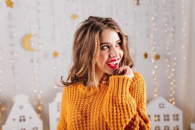 Close-up shot van dromerige romantische dame in oranje trui poseren tegen muur van slingers.