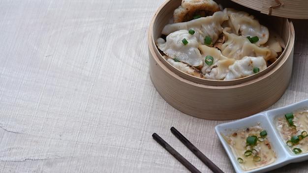 Close-up shot van dumplings in bamboestoomboot met pruimensaus op houten tafel. kopieer ruimte