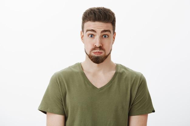 Close-up shot van dwaze en grappige knappe bebaarde man in olijfgroen t-shirt pruilen adem inhouden en eruit zien als een ballon die wenkbrauwen optrekt, zich speels voelen terwijl hij over een witte muur loopt
