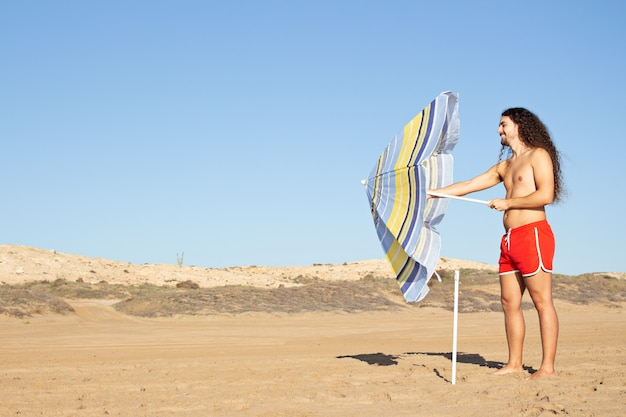 Close-up shot van een aantrekkelijke jonge man met lang krullend haar die een paraplu op het strand aanpast