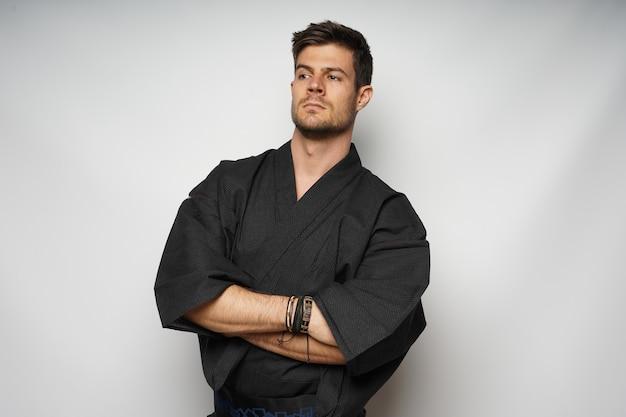 Close-up shot van een aantrekkelijke man staande met gekruiste armen geïsoleerd op witte achtergrond