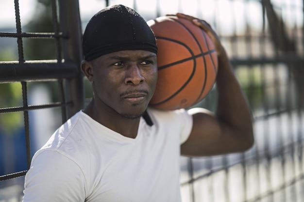 Close-up shot van een afrikaans-amerikaanse man in een wit overhemd met de bal op zijn schouder
