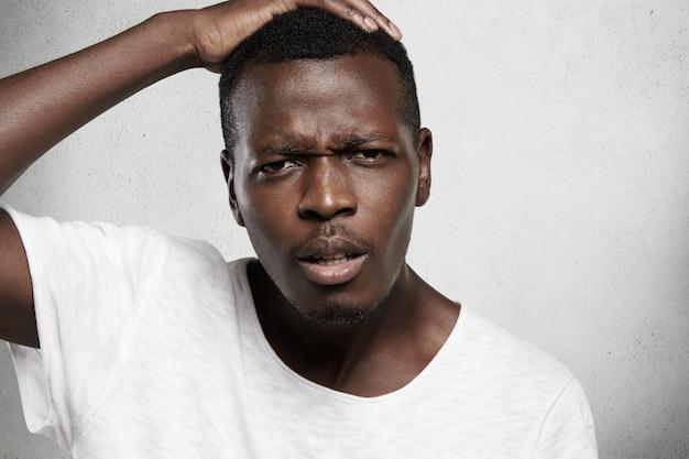 Close-up shot van een afrikaanse man met een wit t-shirt die zijn hoofd vasthoudt, er ontevreden en teleurgesteld uitziet als hij iets verkeerd doet, ongelukkig is met slecht nieuws, fronsend met een verontwaardigde uitdrukking