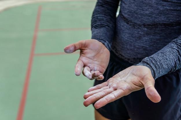 Close-up shot van een atleet die krijt op zijn handen zet - sportconcept