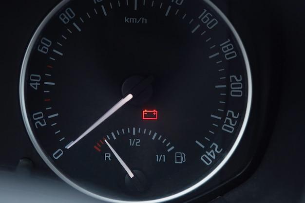 Close-up shot van een autodashboard met het batterijpictogram verlicht