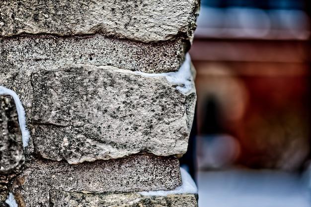 Close-up shot van een bakstenen muur met sneeuw erop