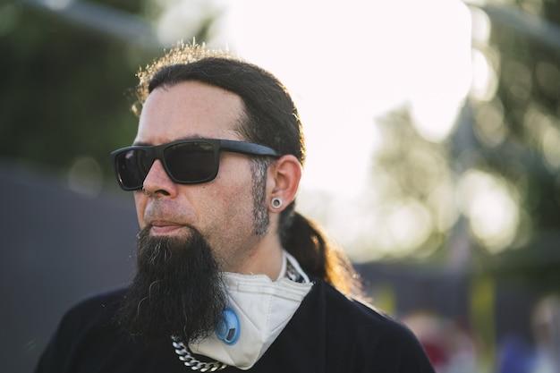 Close-up shot van een bebaarde man met een gezichtsmasker op zijn nek poseren in het park