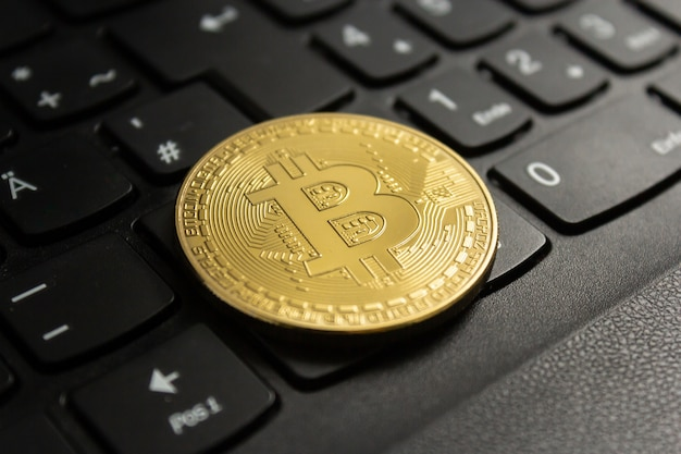 Close-up shot van een bitcoin op een zwart computertoetsenbord