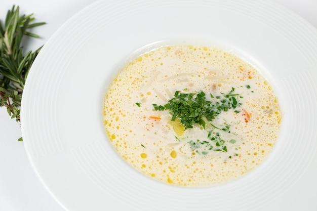 Close-up shot van een bord met witte soep met greens