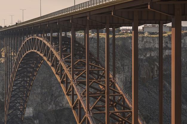 Close-up shot van een brug in het midden van kliffen met stadsgebouwen in de verte overdag