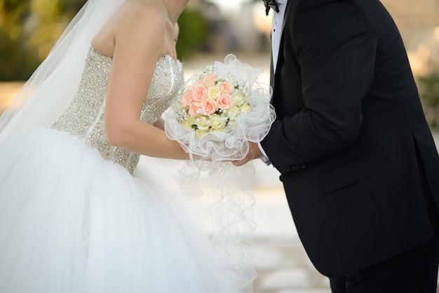 Close-up shot van een bruid en bruidegom die elkaar kussen terwijl ze het prachtige boeket vasthouden