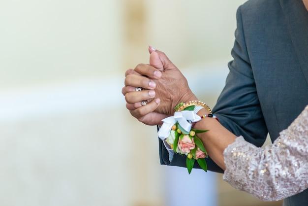 Close-up shot van een bruid en een bruidegom hand in hand tijdens het dansen