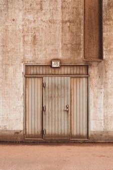 Close-up shot van een bruine houten deur van een betonnen gebouw