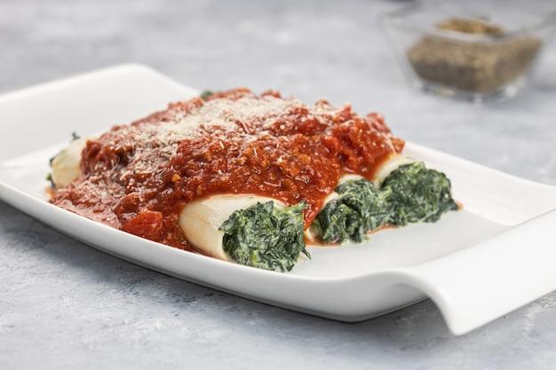 Close-up shot van een cannelloni gerecht gevuld met spinazie en ricotta geserveerd met bolognese saus