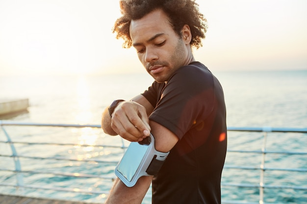 Close-up shot van een donkere mannelijke atleet die mobiele armtas bevestigt. ochtend buitentraining achter de zee. sport, technologie en vrijetijdsconcept.