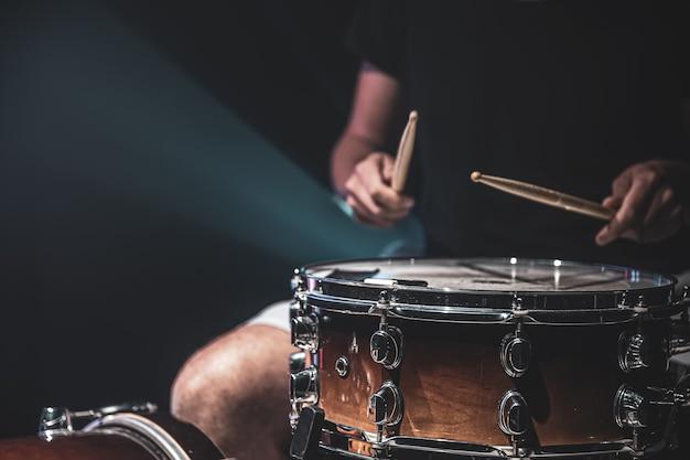 Close-up shot van een drummer die een snaredrum speelt met stokken op een donkere achtergrond.