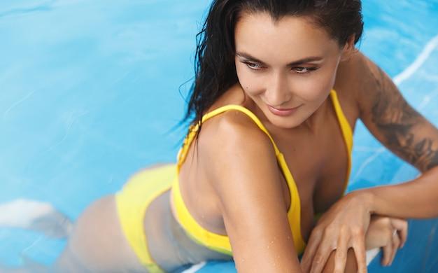 Close-up shot van een gebruinde vrouw met een tatoeage op de schouder, magere zwembadrand, wegdraaien met een verleidelijke en ontspannen glimlach.