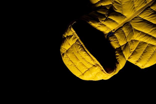 Close-up shot van een geel donsjack op zwarte achtergrond