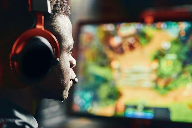 Close-up shot van een gefocuste afrikaanse man, professionele cybersport-gamer met een koptelefoon aan het spelen