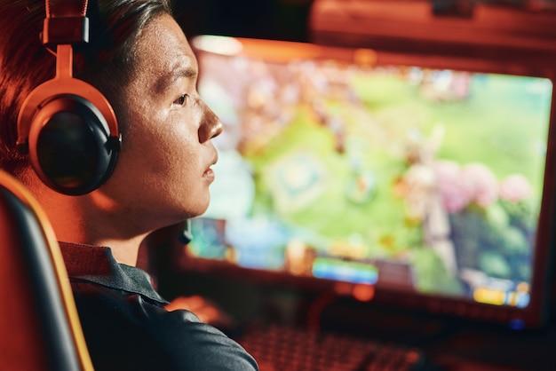 Close-up shot van een gefocuste aziatische man, professionele cybersport-gamer die een koptelefoon draagt die online videogames speelt, achteraanzicht. esport-toernooiconcept