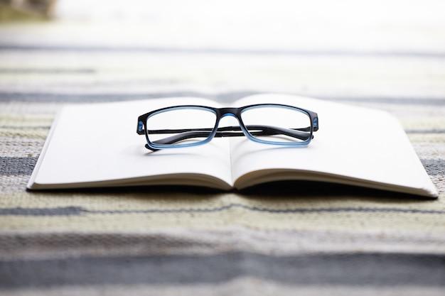 Close-up shot van een geopend notitieboekje met een bril erop