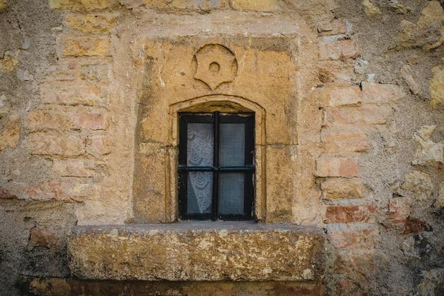 Close-up shot van een gesloten raam op een gele stenen muur