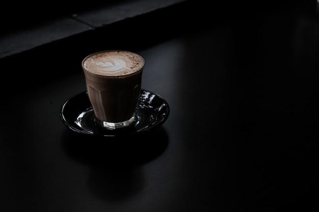 Close-up shot van een glas koffie op een zwarte ondergrond