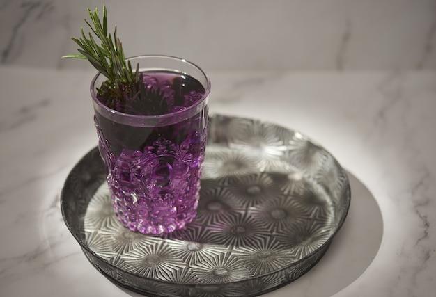 Close-up shot van een glas paarse drank met rozemarijnblaadjes