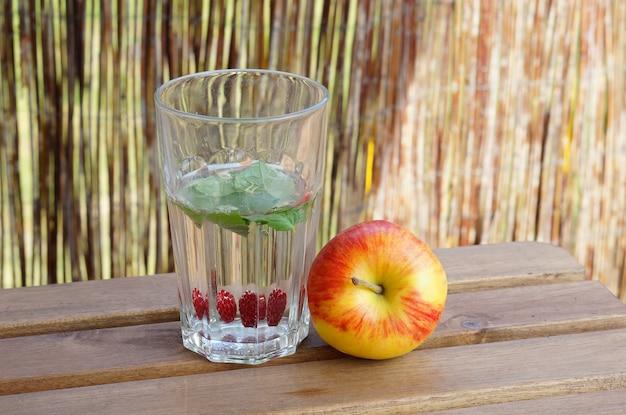 Close-up shot van een glas water met munt en framboos met een appel ernaast