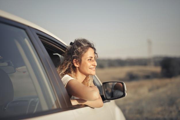 Close-up shot van een glimlachende jonge vrouw die naar buiten kijkt vanuit de auto