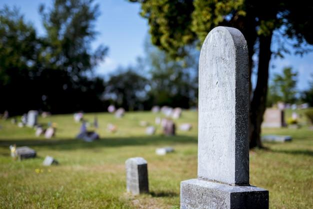 Close-up shot van een grafsteen met een onscherpe achtergrond overdag