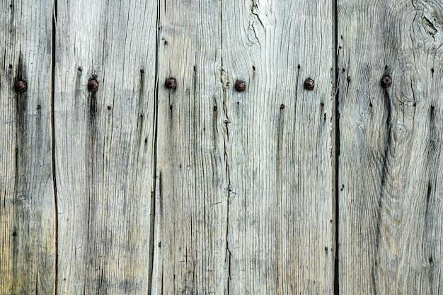 Close-up shot van een grijze houten muur met spijkers erop