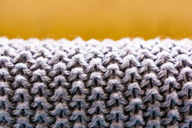 Close-up shot van een grijze pluizige textiel met een wazige bruine achtergrond