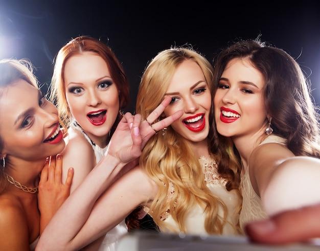 Close-up shot van een groep lachende meisjes die feest hebben, selfie maken met smartphone